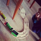 Watch that train. Child is watching his wooden train under the chair Royalty Free Stock Images