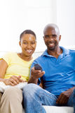 Watch TV. Happy african american couple watch TV on sofa Royalty Free Stock Photography