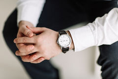 Watch. With white dial on the hand of a man in a white shirt Stock Photo