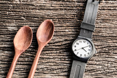 Watch and wooden spoon on table. Top desk watch school supplies still life table Royalty Free Stock Photo