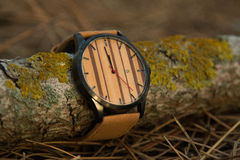 Watch in the woods. Wooden watch with leather in the woods stock photo