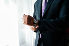 Watch on the wrist of a man. In black suit Stock Photos