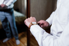 Watch on the wrist of a man in a shirt. Watch on the wrist of a man in a white shirt Royalty Free Stock Images