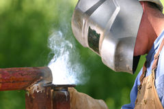 Watch your eyes!. Welder with hood on welding on pipe Royalty Free Stock Photos