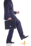 Watch your step. Businessman about to step on a banana skin Royalty Free Stock Photography