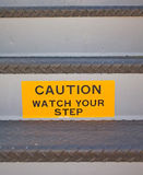 Watch Your Step. A bright yellow sign saying Caution - Watch your Step, on the step of a staircase Royalty Free Stock Image