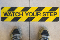 Watch your step construction warning sign. Shoes / feet in front of watch your step warning sign found on concrete and typically seen in construction areas and Stock Photography