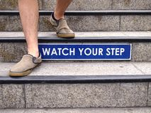 Watch your step sign on a staircase and a pair of feet Royalty Free Stock Photos