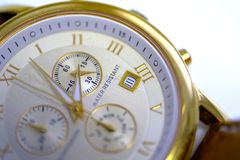 Watches, close up view, time. Close up photo of watches or electronic quartz clock. Typical chronometer face, three smaller dials, date window, golden surface Stock Image