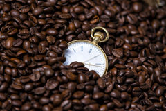 Watches are in coffee beans. Pocket watch half bombarded with coffee beans Stock Photos