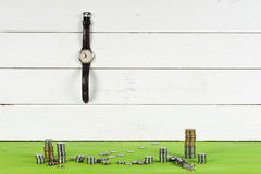 Watches, coins and dollars  on wooden table on bright background. Stock Image