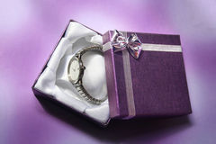 Watches in the gift box. A watch in a purple gift box Royalty Free Stock Photo