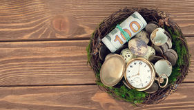 Watches, money, and eggs in a nest Stock Image