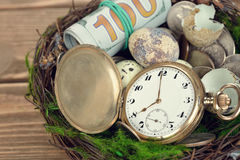 Watches, money, and eggs in a nest Royalty Free Stock Image