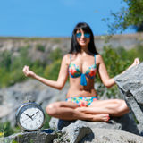 Watches and tanned blurred young woman in bikini sitting in lotu. S position in a mountainous area . Concept of time to relax. Square frame, shallow depth of Royalty Free Stock Images