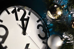 Watches, toys and Christmas tree. Clock showing 12 o`clock, golden and silver ball on the Christmas tree Royalty Free Stock Photo