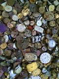 Discarded watches jumbled in a pile. Watch faces and gears of various colors and angles, in aerial view and close up Stock Photography