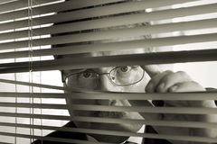 Watchful Eye. Retro looking picture of businessman peering through blinds Stock Photo