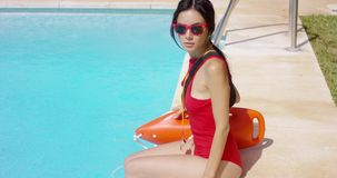 Watchful lifeguard sitting at side of pool stock footage