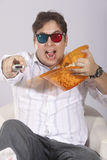 Watching 3D Movie. A young man watching a movie in 3D, with stylish 3D glasses and eating popcorn stock photo