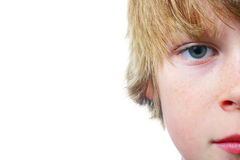 Watching. Closeup of half of a boy's face isolated on a white background with room for copy Stock Photos