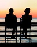 Watching. Couple watching the sun set stock photography