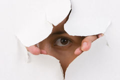 Watching through. A woman's eye watching through the cracked wall Royalty Free Stock Photo