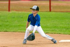 Watching the ball into the glove. Youth baseball player in blue uniform covering second base and waiting for the ball in the infield during a game royalty free stock photos