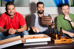 Watching a baseball game at night. Three Hispanic male friends eating pizza and drinking beer while watching a baseball game at night Stock Photo