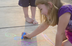 Watching big sister draw. A young girl drawing with chalk on a light colored driveway while her younger brother watches Royalty Free Stock Image