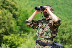 Watching with binoculars. The smiling man in military uniform is watching with binoculars in nature on greenery background Stock Photography