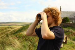 Watching birds. Young man watching birds with binoculars Stock Images
