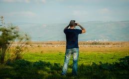 Watching birds. Young man watching birds with binoculars Royalty Free Stock Photography