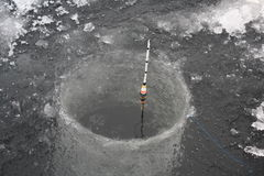 Watching the bobber. An ice fishing bobber waits for the fish to bite Royalty Free Stock Photography