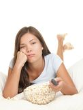 Watching boring movie. Girl bored watching boring movie in bed. Funny image of woman lying down in bed on White background eating popcorn and zapping changing stock photo