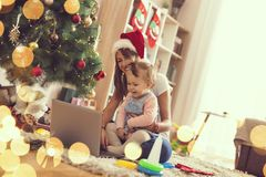 Watching cartoons. Mother and daughter sitting on the floor next to a Christmas tree, watching cartoons on a laptop computer and having fun. Focus on the baby stock photos