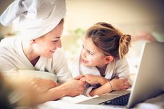 Watching cartoons with Mother online. Little girl. Lifestyle stock photo