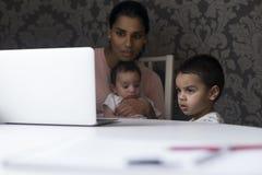 Watching cartoons on mums laptop Royalty Free Stock Photos