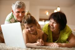 Watching cartoons with my grandparents. Little girl. Home activity. Close up image stock photos
