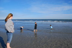 Watching the Children. A babysitter watches the children as they play in the shallow water Stock Images