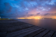 Watching the City lights. Distant city lights watched from a wooden pier Stock Photos
