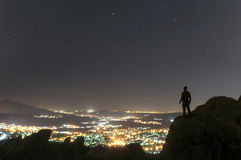Watching the city from the mountain at night-5. Man on top of a mountain and enjoying night sky view and city lights Stock Image