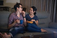 Watching comedy. Laughing Asian couple eating popcorn and watching comedy movie Stock Photos