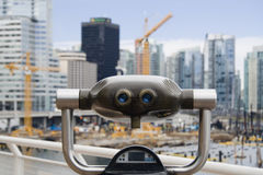 Watching a construction site. Binocular with an out of focus construction site in the background stock image