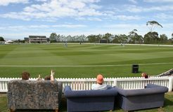 Watching the cricket. Industrious spectators who dragged out some couches to watch an International cricket match between the India and New Zealand woman's stock image