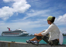 Watching Cruise Ships. The girl watching a cruise liner that is arriving to Nassau town port, the capital of The Bahamas Stock Photos