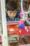 Watching 3D printer intently. Stock Photo