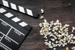 Watching the film. Movie clapperboard and popcorn on wooden table background top view copyspace Stock Photos