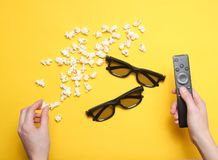 Watching films. Flat lay style hands holding tv remote, popcorn, two pair 3d glasses on yellow background. Minimalism. Top view royalty free stock photography