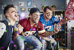 Watching football game. American football fans among falling confetti stock photos